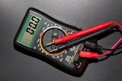 Digital multimeter with probes. Closeup on a black background Stock Photography