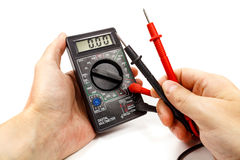 Digital multimeter with probes in man`s hand on a white background Royalty Free Stock Photo
