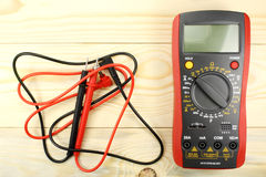 Digital multimeter with probes on a wooden table Royalty Free Stock Photography