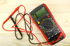 Digital multimeter with probes on a wooden table Royalty Free Stock Photos