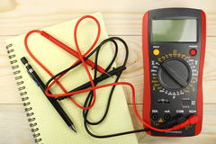 Digital multimeter with probes on a wooden table Royalty Free Stock Images