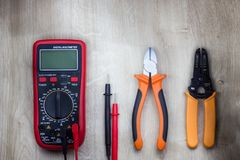 Digital multimeter, side cutters and cable stripper. Top view of work tools for residential electrical installation on wooden background. Close-up Stock Photos
