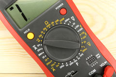 Digital multimeter on a wooden table closeup stock images