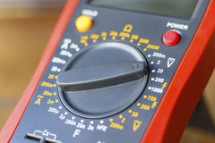 Digital multimeter on a wooden table in the workshop closeup Royalty Free Stock Images