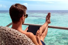 Young man in swimsuit working on a tablet in a tropical destination royalty free stock images