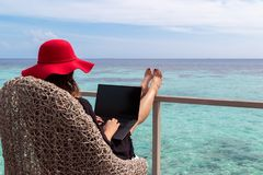 Young woman with red hat working on a computer in a tropical destination royalty free stock image