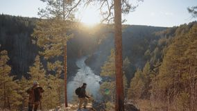 Digital nomad on a rock overlooking a mountain river in a pine forest at sunset. unity with nature. Unity with nature digital nomad on a rock overlooking a stock video footage