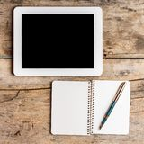 Digital pad with empty black screen and opened notebook Royalty Free Stock Photos