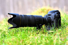 Digital photo camera. Black digital photo camera in grass royalty free stock photo
