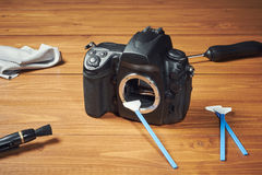 Digital photo camera with cleaning tools Royalty Free Stock Photos