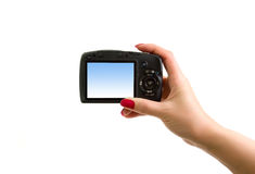 Digital photo camera in hand. Over the white background royalty free stock photos