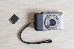 Digital photo camera and SD card. Photo camera at white wooden background Stock Images