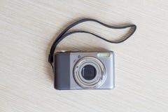 Digital photo camera. Photo camera at white wooden background Royalty Free Stock Photos