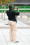Digital Photo Man. Black man taking a digital picture while carrying his baby Royalty Free Stock Image