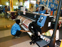 Digital printing. Engineers are showing the way digital printing machine operating in an exhibition in the city of Solo, Central Java, Indonesia royalty free stock images