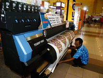 Digital printing. Engineers are showing the way digital printing machine operating in an exhibition in the city of Solo, Central Java, Indonesia stock photos