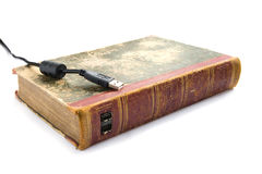 Digital revolution. An old book with two USB ports and an USB cable next to it, symbolizing the digital revolution and technical progress stock image