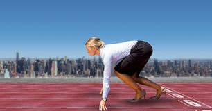 Digital sammansatt bild av affärskvinnan på startande linje av loppspår i stad mot himmel Arkivfoto