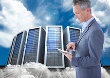 Digital sammansatt bild av affärsmannen som använder den digitala minnestavlan mot servertorn Arkivbild