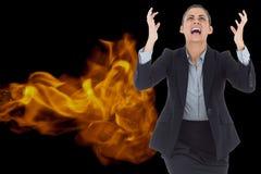 Digital sammansatt bild av den ilskna affärskvinnan som skriker med brand i bakgrund arkivfoto