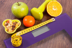 Digital scale with tape measure, dumbbells, fruits, muesli, slimming concept Stock Image