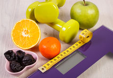 Digital scale with tape measure, dumbbells, fruits, slimming concept Stock Image