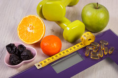 Digital scale with tape measure, dumbbells, tablets, fruits, slimming concept royalty free stock photos