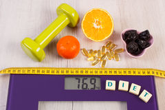 Digital scale with tape measure, dumbbells, tablets, fruits, slimming concept Stock Photography