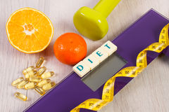 Digital scale with tape measure, dumbbells, tablets, fruits, slimming concept Royalty Free Stock Images