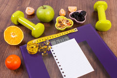 Digital scale with tape measure, tablets, dumbbells, fruits, muesli, slimming concept Stock Images