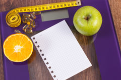 Digital scale with tape measure, tablets and fresh fruits, slimming concept Royalty Free Stock Image