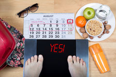 Digital scales with female feet sign `yes!` surrounded by calendar, summer accessories and plate with healthy food. Digital scales with female feet on them and Royalty Free Stock Photos