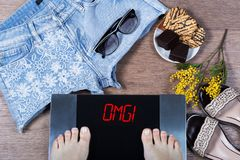 Digital scales with female feet on them and sign omg! surrounded by mimosa flowers, shorts and sweets. Royalty Free Stock Images