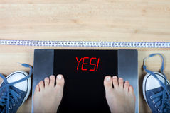 Digital scales with female feet on them and sign surrounded by gymshoes and measuring tape. Digital scales with female feet on them and sign`yes!` surrounded by stock image