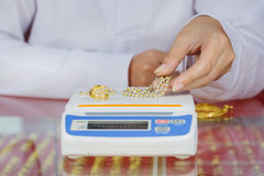 Digital scales for weighing gold rings and necklaces with hand. In store Royalty Free Stock Photography