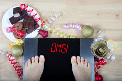 Digital scales with woman feet on them and sign sign`OMG!` surrounded by christmas decorations and unhealthy food. Digital scales with woman feet on them and Royalty Free Stock Images