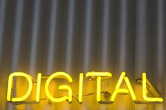 Digital Sign. A bright yellow neon sign on a corrugated metal building says DIGITAL Stock Images