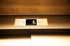 Digital skärm med den ovannämnda hissdörren för nummer sex Royaltyfri Foto
