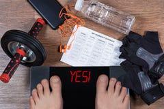 Digital-Skalen mit männlichen Füßen auf ihnen und Zeichen ` ja! ` umgeben durch Rollenrad des Sportzubehörs AB, Trainingszeitplan Lizenzfreies Stockfoto