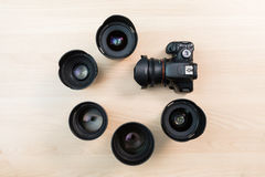 Digital SLR camera and a few interchangeable manual lenses. The equipment for filmmaking. The wooden table Stock Images