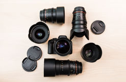 Digital SLR camera and a few interchangeable manual lenses. The equipment for filmmaking. The wooden table Stock Photography