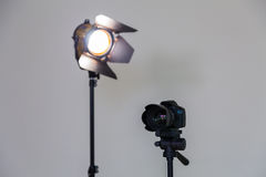 Digital SLR camera and a spotlight with a Fresnel lens on a gray background. Shooting in the interior Royalty Free Stock Photography
