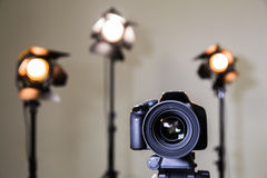 Digital SLR camera and three spotlights with Fresnel lenses. Manual interchangeable lens for filming. Shooting in the interior with artificial light. Equipment stock images