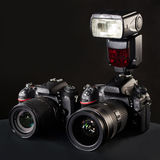Digital SLR cameras, lens and flash on black stock image