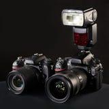 Digital SLR cameras, lens and flash on black Stock Image