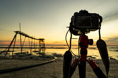 Digital SLR and wooden structure over beautiful light during sunset Royalty Free Stock Photo