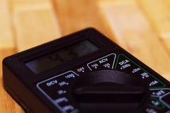 Digital som mäter multimeteren på trägolv Det visar 4 33V eller fullständigt laddat batteri Inkluderar voltmetern, ampermeteren,  royaltyfria foton