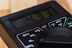 Digital som mäter multimeteren på trägolv Det visar 4 33V eller fullständigt laddat batteri Inkluderar voltmetern, ampermeteren,  royaltyfri fotografi