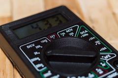 Digital som mäter multimeteren på trägolv Det visar 4 33V eller fullständigt laddat batteri Inkluderar voltmetern, ampermeteren,  royaltyfri foto