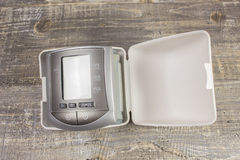 Digital sphygmomanometer blood pressure monitor on background of wooden table. Tonometer Royalty Free Stock Photos